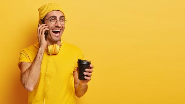 Szczęśliwy młody człowiek dobrze rozmawia przez telefon komórkowy, trzyma kawę na wynos, lubi drinka, ubrany w casualową koszulkę i kapelusz