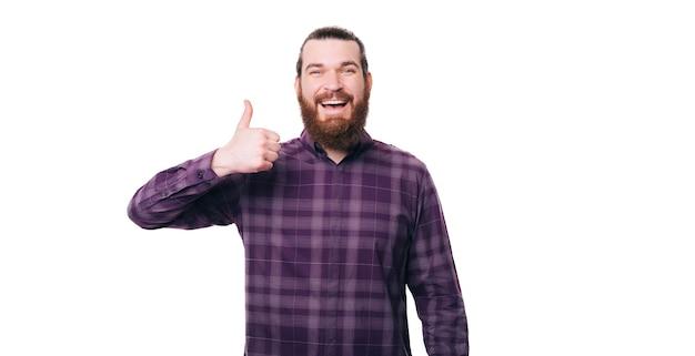 Szczęśliwy młody człowiek dorywczo pokazuje kciuk nad białą ścianą