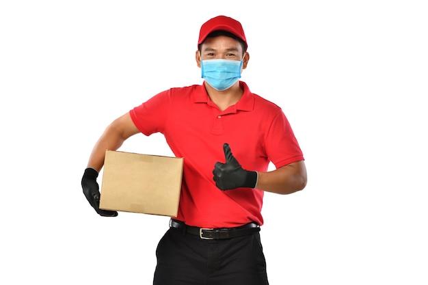 Szczęśliwy młody człowiek dostawy azjatyckich w czerwonym mundurze, maska medyczna, rękawice ochronne nosić karton w rękach na białym tle. dostawca dostarcza paczkę. bezpieczna dostawa