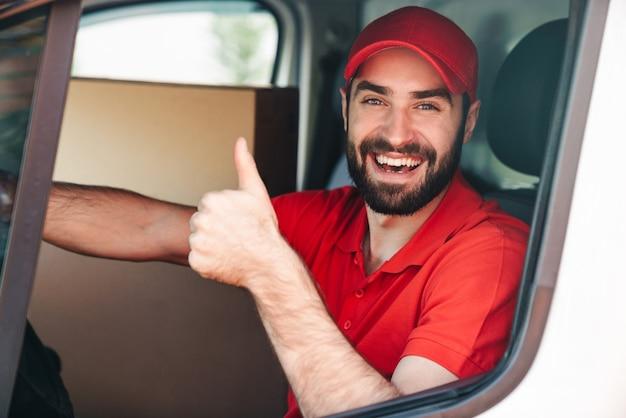 Szczęśliwy młody człowiek dostawy w czerwonym mundurze pokazując kciuk do góry i jadący furgonetką z pudłami do paczek