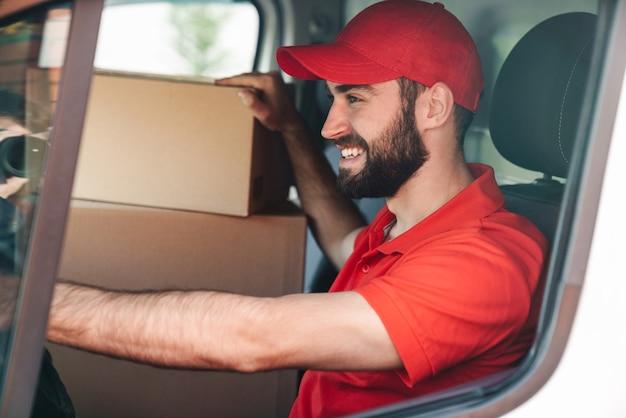 Szczęśliwy młody człowiek dostawy w czerwonym mundurze uśmiechający się i prowadzący furgonetkę z pudłami do paczek