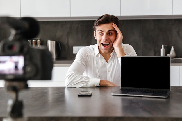 Szczęśliwy młody człowiek filmujący swój odcinek blogu wideo