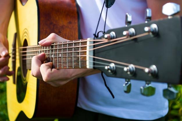 Szczęśliwy młody człowiek gra na gitarze poza domem