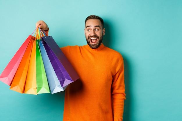 Szczęśliwy młody człowiek idzie na zakupy, trzymając torby i patrząc podekscytowany, stojąc w pomarańczowym swetrze stojącym przed turkusową ścianą