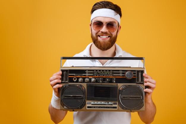 Szczęśliwy młody człowiek jest ubranym okulary przeciwsłonecznych trzyma taśma pisaka
