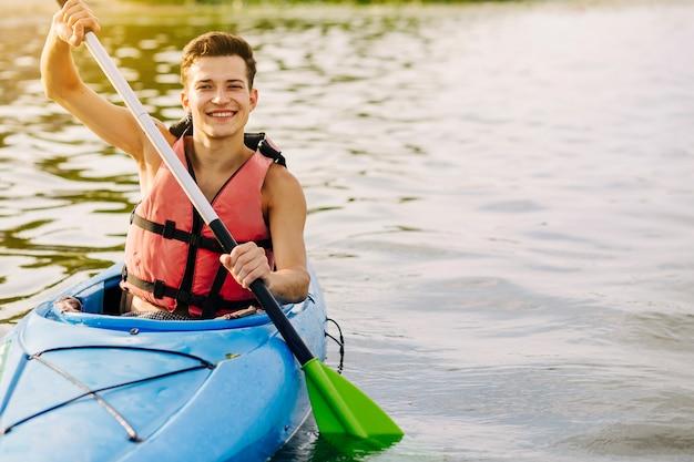 Szczęśliwy młody człowiek kayaking na jeziorze