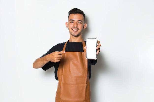 Szczęśliwy młody człowiek kelnerka barista trzyma telefon komórkowy z pustym pustym ekranem