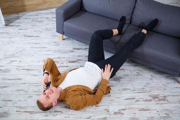 Szczęśliwy młody człowiek leżący na podłodze w pobliżu kanapy w salonie i odpoczywający