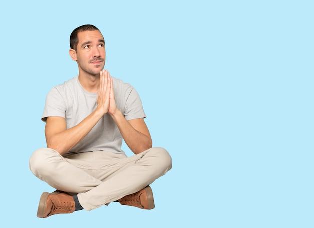 Szczęśliwy młody człowiek modlący się gest
