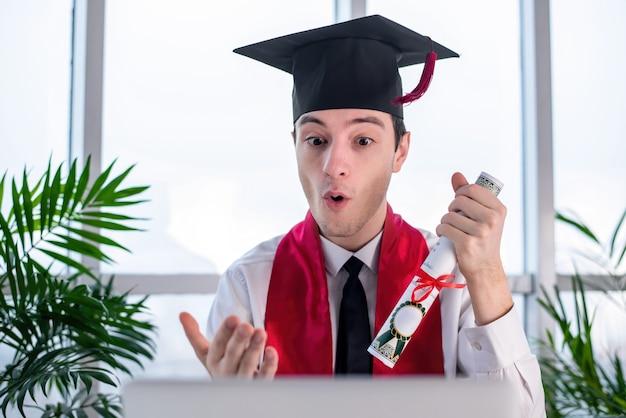 Szczęśliwy młody człowiek mówi i gestykuluje na ukończeniu uniwersytetu online w swoim laptopie z przewijaniem w ręce