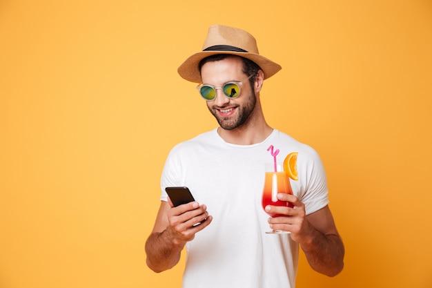 Szczęśliwy młody człowiek na czacie przez telefon komórkowy gospodarstwa koktajl.