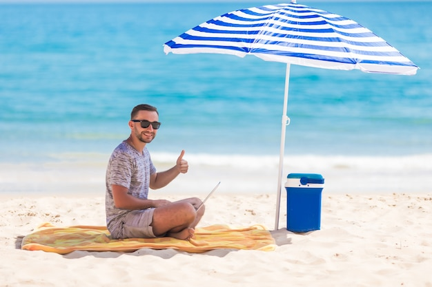 Szczęśliwy młody człowiek na plaży pod parasolem w pobliżu oceanu pracuje na swoim laptopie i pokazuje kciuk w górę