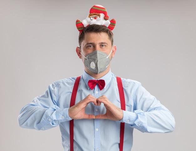 Szczęśliwy młody człowiek nosi muszkę do szelek w obręczy z mikołajem w ochronnej masce na twarz, patrząc na kamerę, która robi gest serca palcami stojąc na białym tle