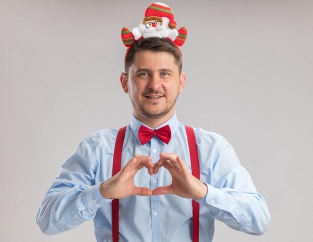 Szczęśliwy młody człowiek nosi muszkę w szelkach w obręczy z mikołajem patrząc na kamerę robi gest serca palcami uśmiechając się radośnie stojąc na białym tle