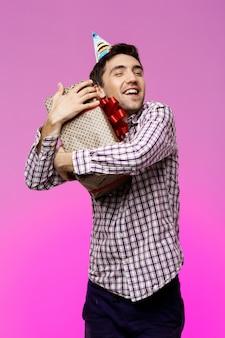 Szczęśliwy młody człowiek obejmuje prezent urodzinowy w pudełku nad purpury ścianą.