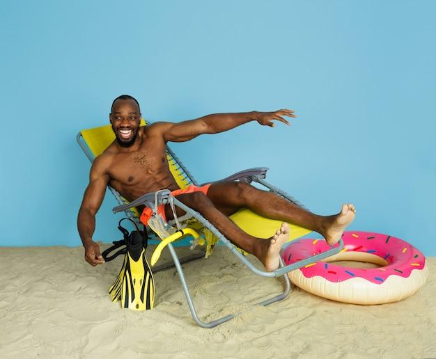 Szczęśliwy młody człowiek, odpoczynek i śmiech z pierścieniem plaży jako pączek na niebieskiej przestrzeni