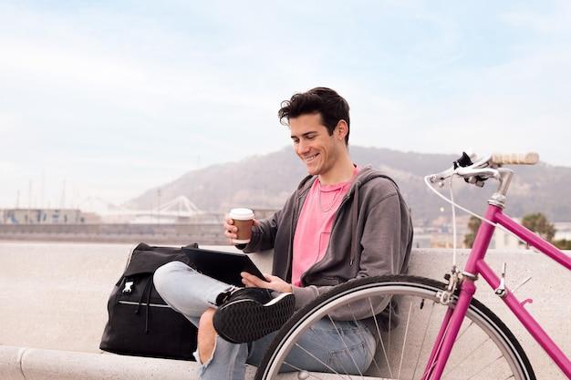 Szczęśliwy młody człowiek ogląda wideo na tablecie na zewnątrz