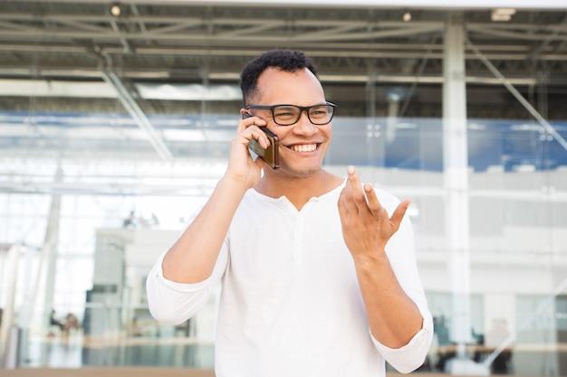 Szczęśliwy młody człowiek opowiada na smartphone i gestykuluje outdoors