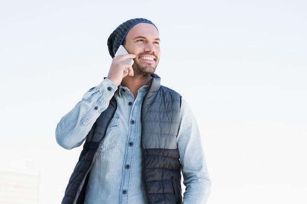 Szczęśliwy młody człowiek opowiada na telefonie komórkowym na białym tle