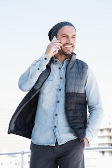 Szczęśliwy młody człowiek opowiada na telefonie komórkowym