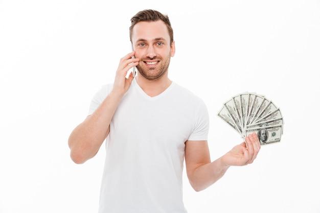 Szczęśliwy młody człowiek opowiada telefonem komórkowym.