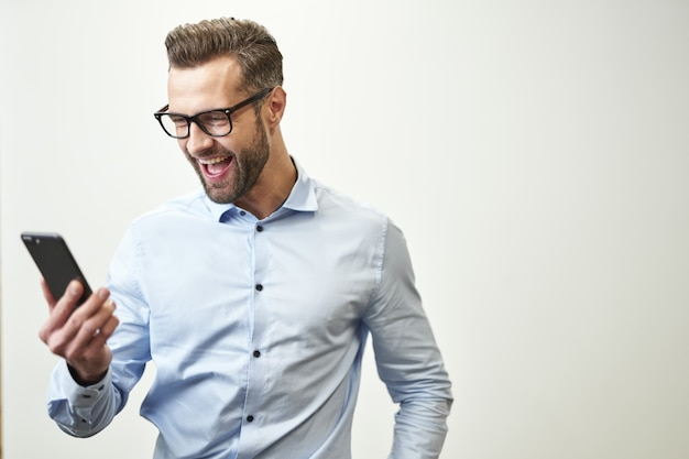 Szczęśliwy młody człowiek patrząc na ekran swojego telefonu i wyrażając emocje. baner strony internetowej