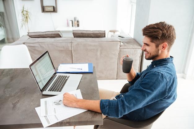 Szczęśliwy młody człowiek pije kawę siedząc przy stole z dokumentami i laptopem. patrząc na laptopa