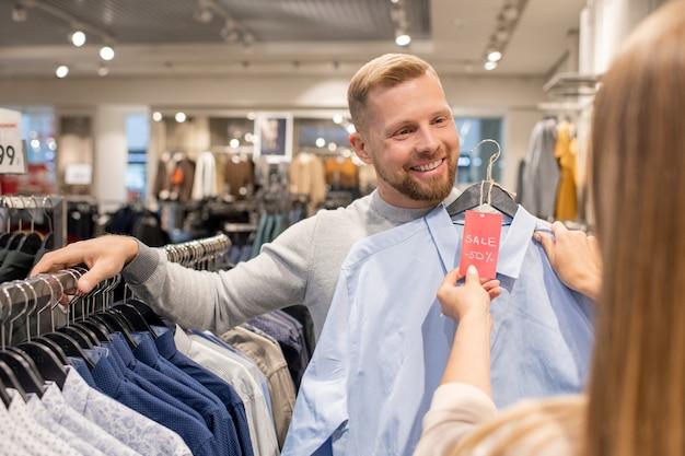 Szczęśliwy młody człowiek pokazujący swoją dziewczynę niebieską koszulę z pięćdziesięcioprocentowym rabatem, stojąc przy szafie w dziale casual