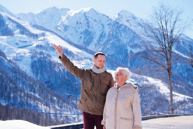 Szczęśliwy młody człowiek pokazuje swojej babci piękne zaśnieżone góry. starsza siwowłosa kobieta uśmiecha się i przytula wnuka. przyjaźń młodszego pokolenia i starszego.