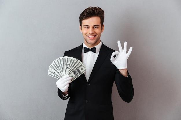 Szczęśliwy młody człowiek pokazuje zadowalającego gesta mienia pieniądze.