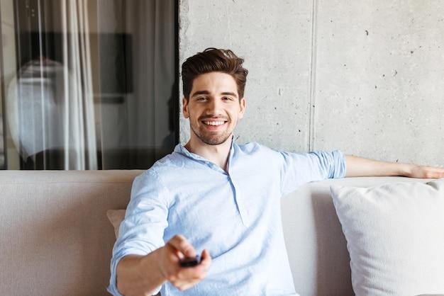 Szczęśliwy młody człowiek posiadający pilota do telewizora
