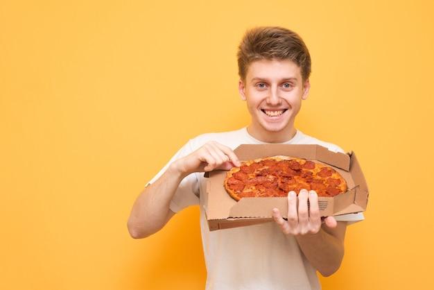 Szczęśliwy młody człowiek posiadający pudełko świeżej pizzy z dostawy