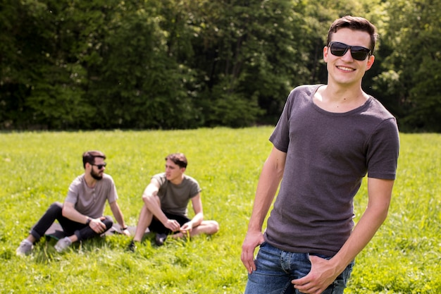 Szczęśliwy młody człowiek pozuje na łące z przyjaciółmi