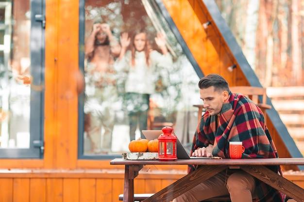 Szczęśliwy młody człowiek pracuje na laptopie i picia kawy, siedząc przy drewnianym stole na zewnątrz