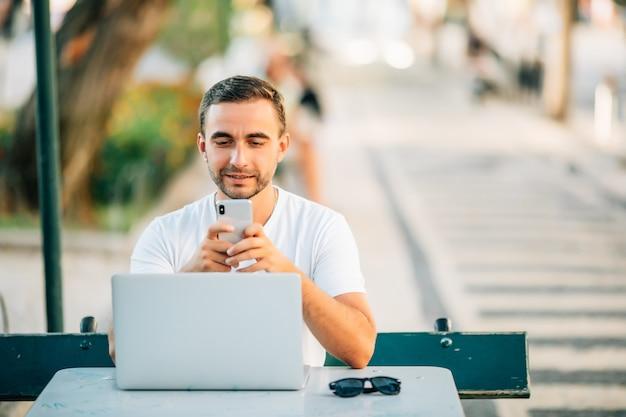 Szczęśliwy młody człowiek pracuje na laptopie i rozmawia przez telefon komórkowy, siedząc przy drewnianym stole na zewnątrz