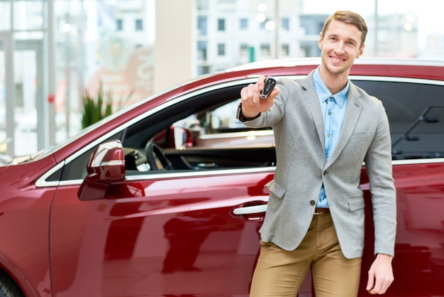 Szczęśliwy młody człowiek przedstawia kluczyki do samochodu