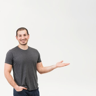 Szczęśliwy młody człowiek przedstawia nad białym tłem