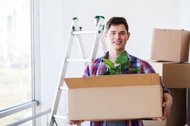 Szczęśliwy młody człowiek przenosi się do nowego domu