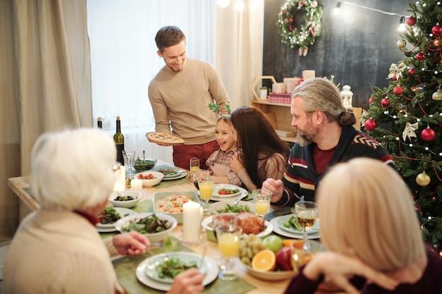 Szczęśliwy młody człowiek przynoszący domowe ciasto dla swojej dużej rodziny, bawiąc się przy świątecznym stole i ciesząc się świąteczną kolacją