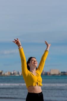 Szczęśliwy młody człowiek radośnie podnosi ręce na brzegu plaży na tle błękitnego morza