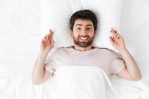 Szczęśliwy młody człowiek rano pod kocem w łóżku kłamie z nadzieją gestem