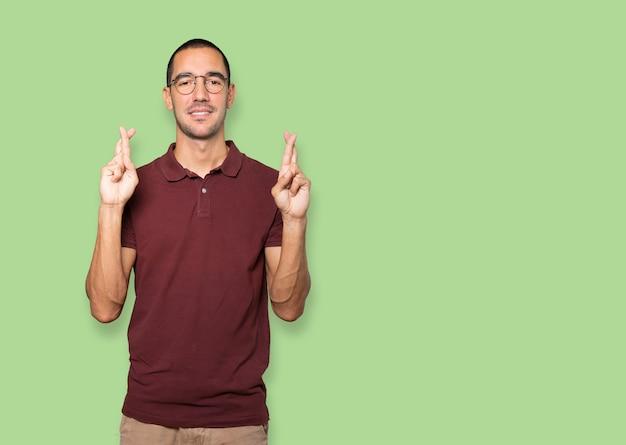 Szczęśliwy młody człowiek robi gest ze skrzyżowanymi palcami