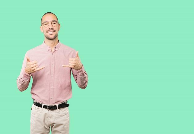 Szczęśliwy młody człowiek robi gestowi dzwonić z ręką
