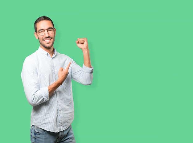 Szczęśliwy młody człowiek robi konkurencyjnemu gestowi