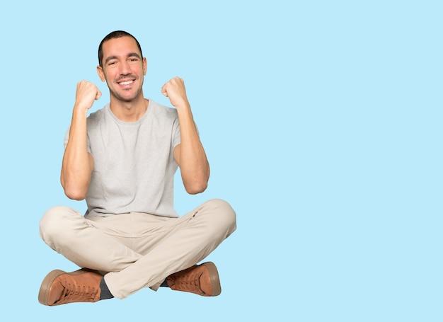 Szczęśliwy młody człowiek robi konkurencyjny gest
