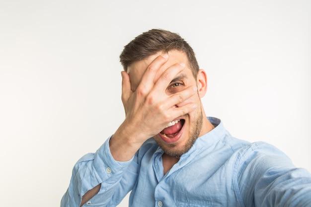 Szczęśliwy młody człowiek robi zdjęcie selfie z emocją dłoni na twarzy