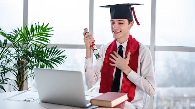 Szczęśliwy młody człowiek rozmawia i zaczyna na ukończeniu uniwersytetu online w swoim laptopie z przewijaniem w ręce