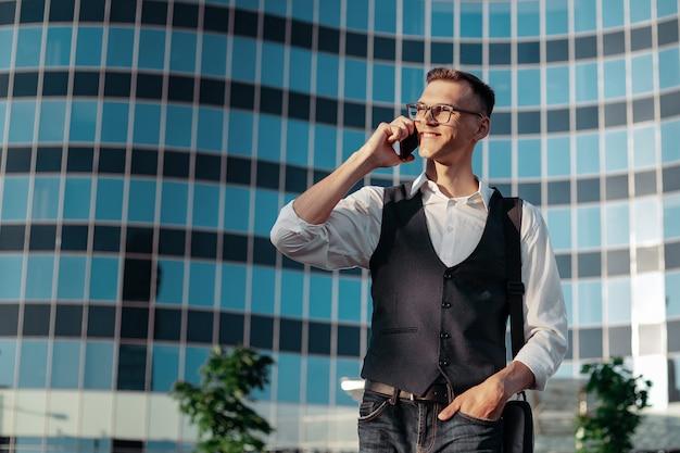 Szczęśliwy młody człowiek rozmawia na smartfonie przed budynkiem biurowym. zdjęcie z kopią - spacja.