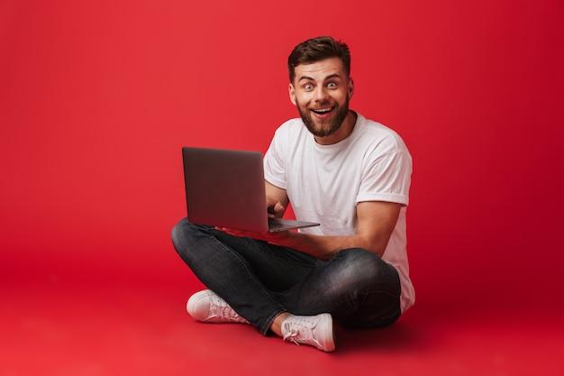 Szczęśliwy młody człowiek siedzi na białym tle przy użyciu komputera przenośnego.