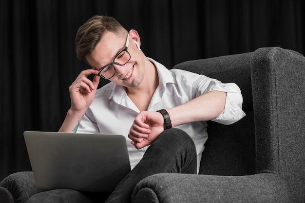 Szczęśliwy młody człowiek siedzi na czarnym fotelu trzymając laptopa na kolanach, patrząc na czas